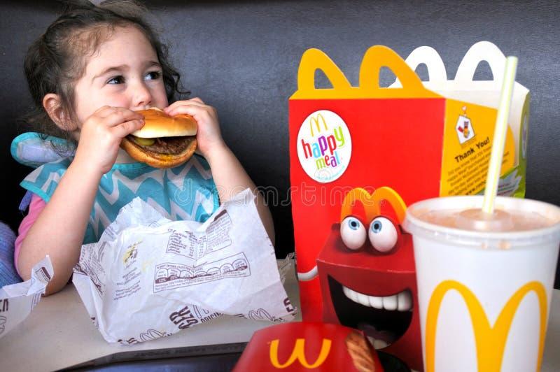 Lilla flickan äter snabbmat royaltyfria foton