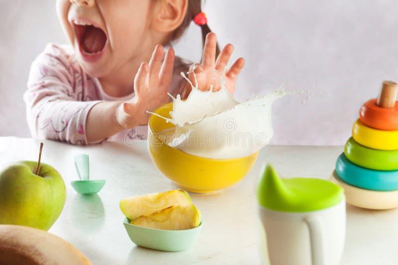 Lilla flickan önskar inte att äta hennes frukosthavregröt arkivfoton