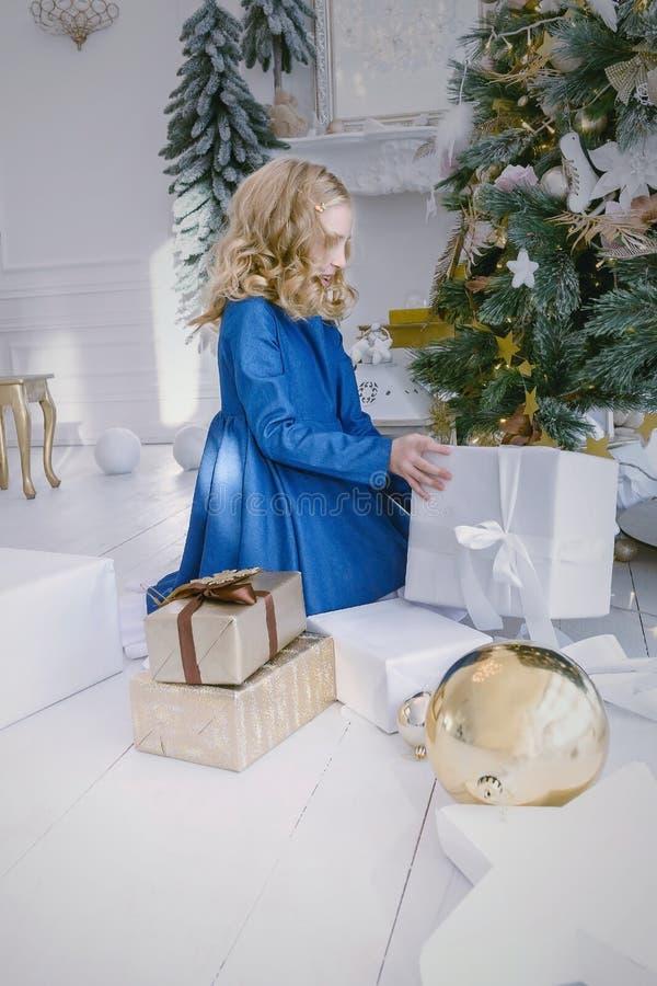 Lilla flickan öppnar asken med gåvor Jul och leksaker och gåvor för nytt år royaltyfri foto