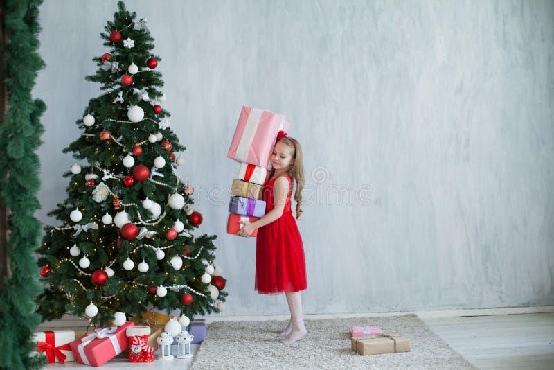 Lilla flickan öppnar julgåvor på huset för ferie för det nya året för julgranen royaltyfri fotografi