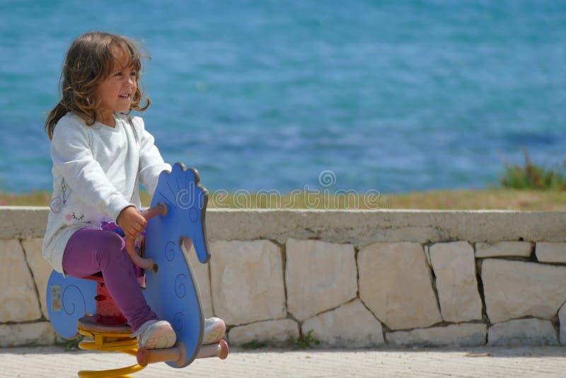 Lilla flickan av 3-4 år spelar lyckligt i en lekplats arkivbild
