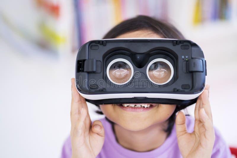 Lilla flickan bär virtuell verklighetexponeringsglas i fel väg arkivbild