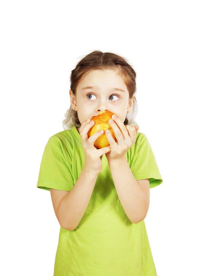Lilla flickan biter ett stort rött äpple och ser åt sidan royaltyfri foto