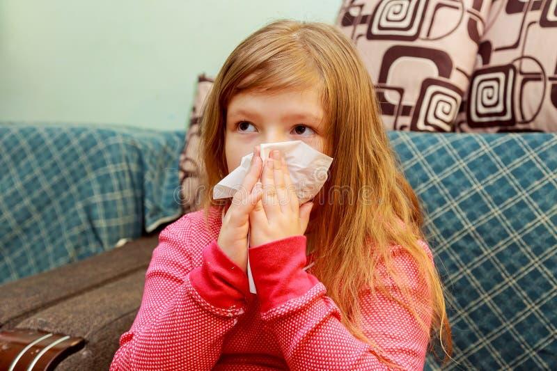 Lilla flickan blåser hans näsa i ett pappers- silkespapper royaltyfri foto