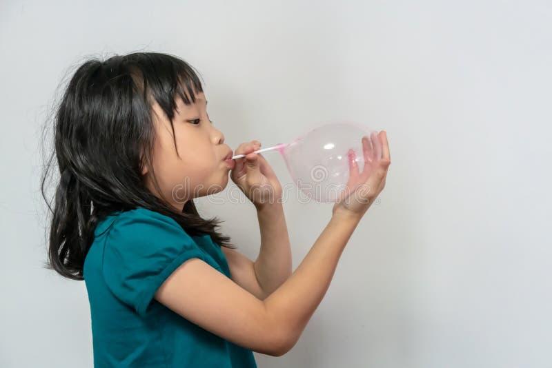 Lilla flickan blåser upp en rosa ballong genom att använda vitt plast- sugrör som isoleras på vit royaltyfria bilder