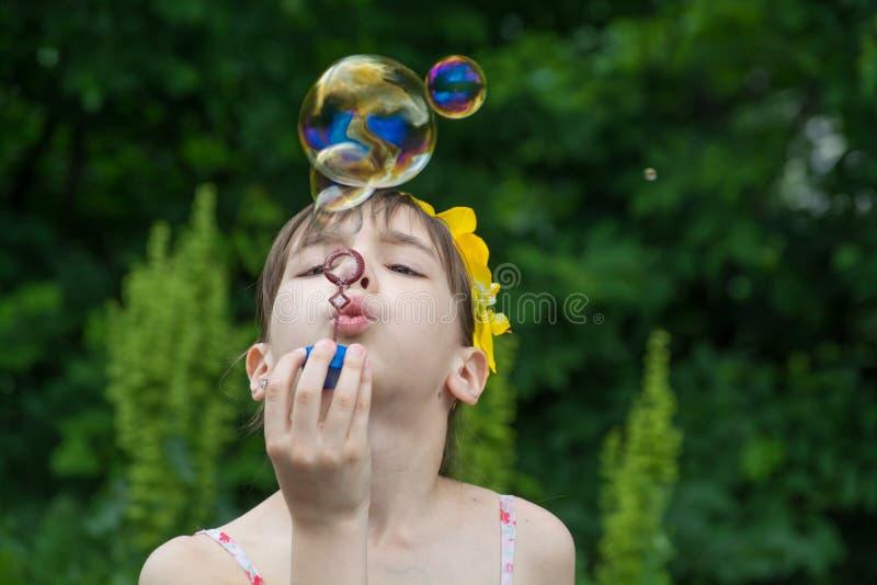 Lilla flickan blåser upp såpbubblor royaltyfri bild