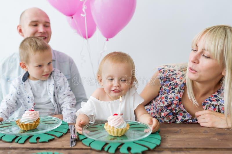 Lilla flickan blåser ut stearinljuset på födelsedagen Födelsedagparti i familj royaltyfri fotografi