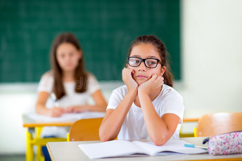 Lilla flickan borras i klassrumet royaltyfria bilder