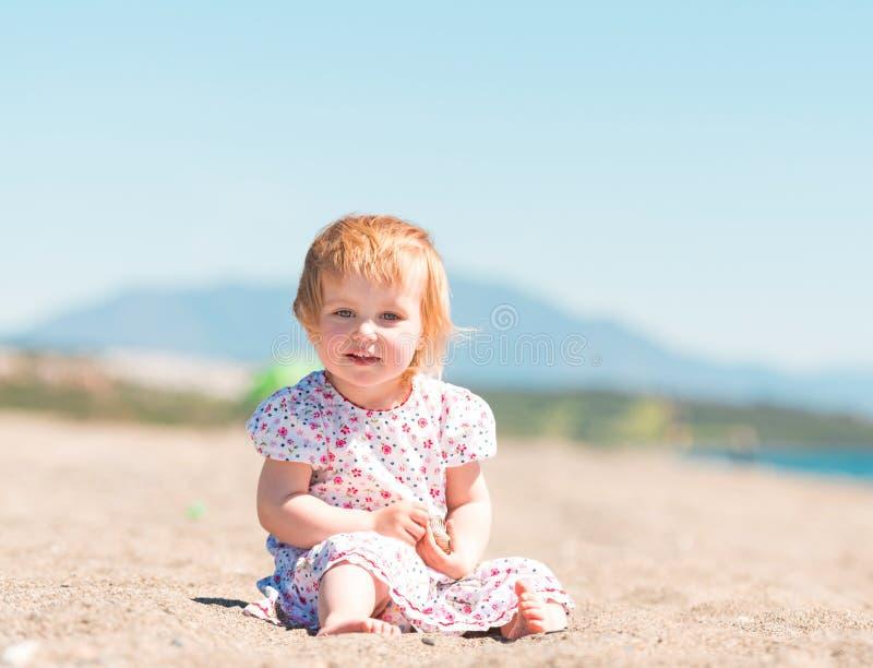 Lilla flickan bygger ett torn av sand royaltyfri foto