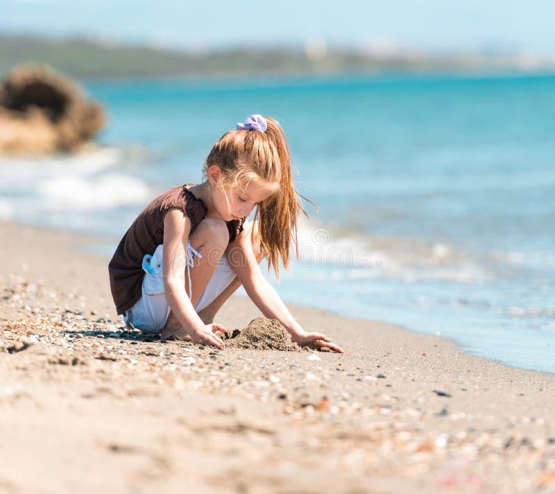 Lilla flickan bygger ett torn av sand arkivbild
