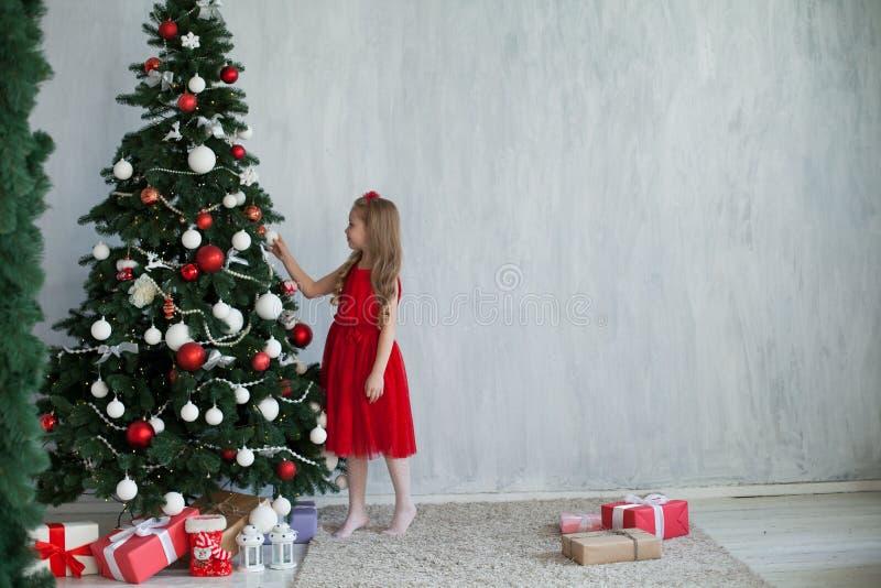Lilla flickan dekorerar gåvor för ett hus för ferie för nytt år för julgran fotografering för bildbyråer