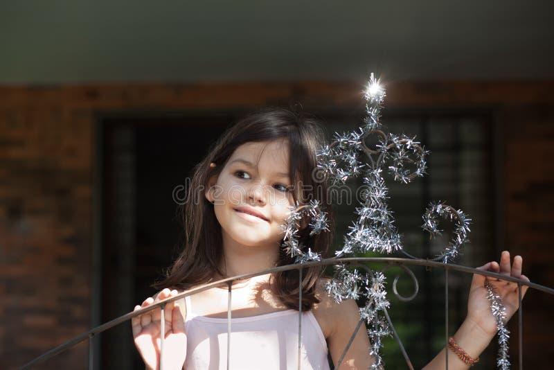 Lilla flickan dekorerar porten av huset fotografering för bildbyråer