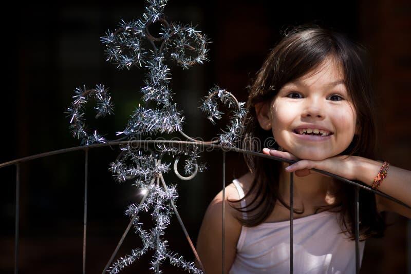 Lilla flickan dekorerar porten av huset arkivbild