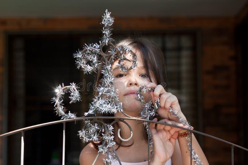 Lilla flickan dekorerar porten av huset royaltyfri foto