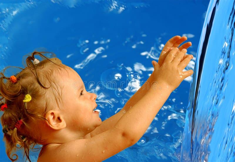 Lilla flickan drar handtaget till vattnet arkivbilder