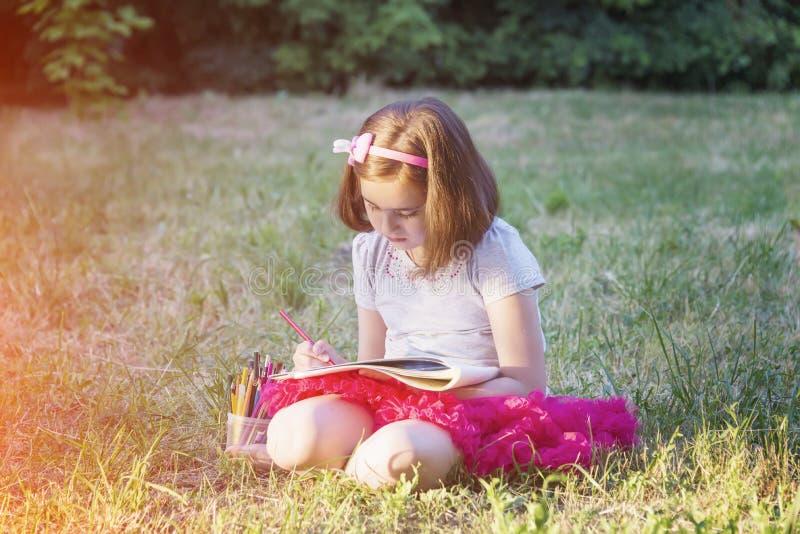 Lilla flickan drar sammanträde på gräset royaltyfri foto