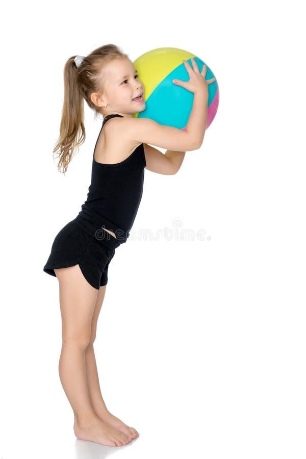 Lilla flickan fångar bollen royaltyfria bilder