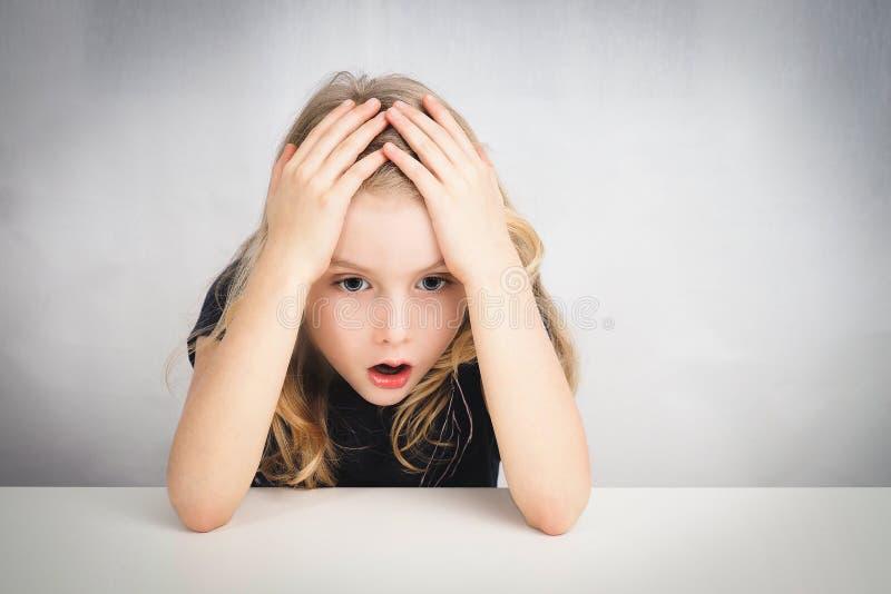 Lilla flickan förbluffade sammanträde på en tabell fotografering för bildbyråer