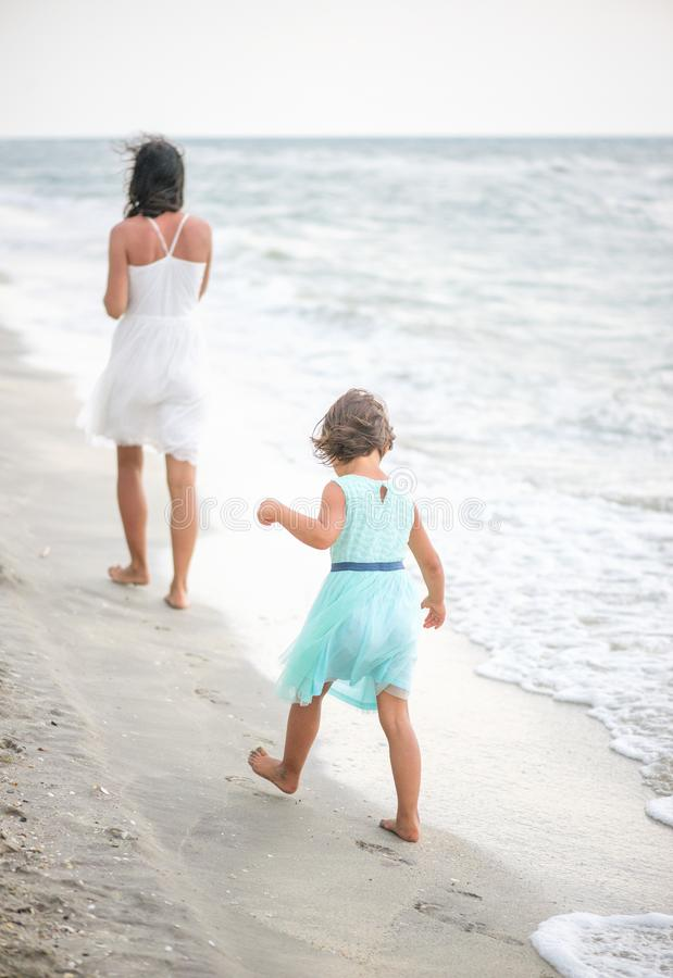 Lilla flickan försöker att gå i fotstegen av hennes moder royaltyfri bild