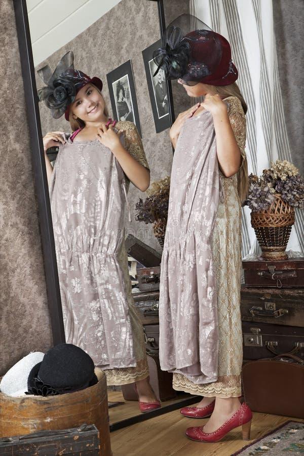 Lilla flickan försöker på en mormorklänning arkivbild