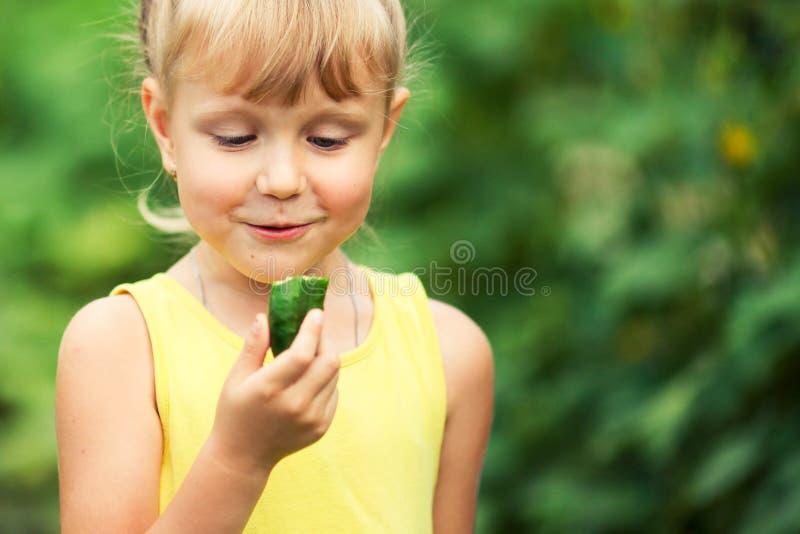 Lilla flickan förvånade att se en gurka royaltyfri foto