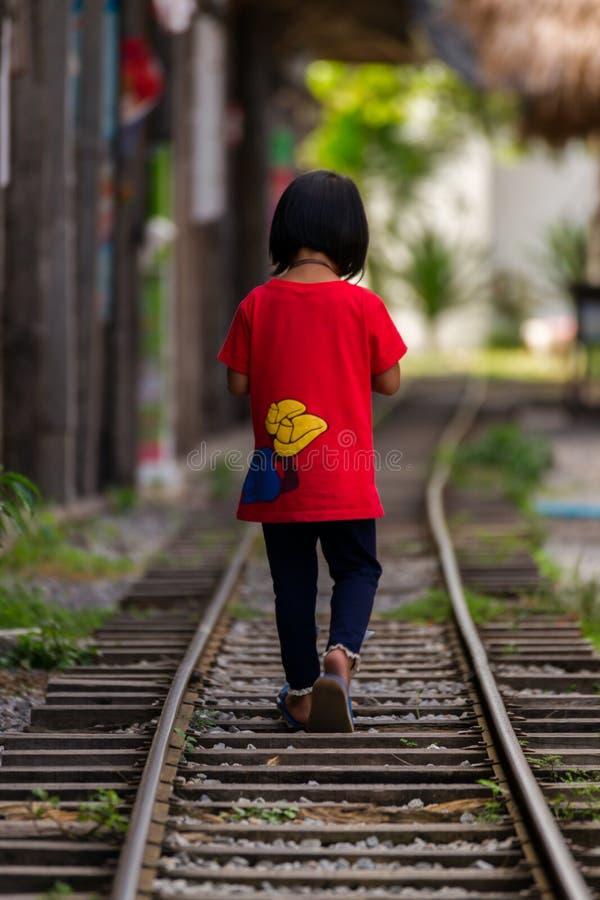 Lilla flickan går på järnvägen royaltyfri foto