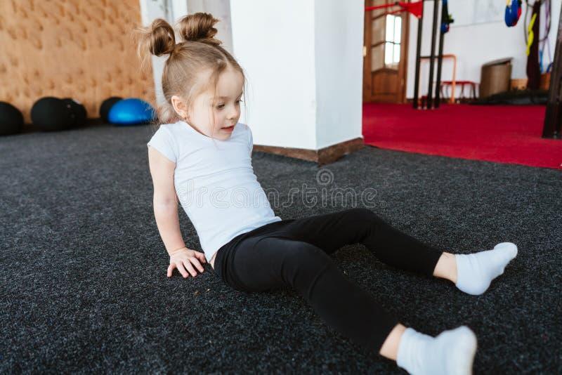 Lilla flickan gör övningar royaltyfri fotografi