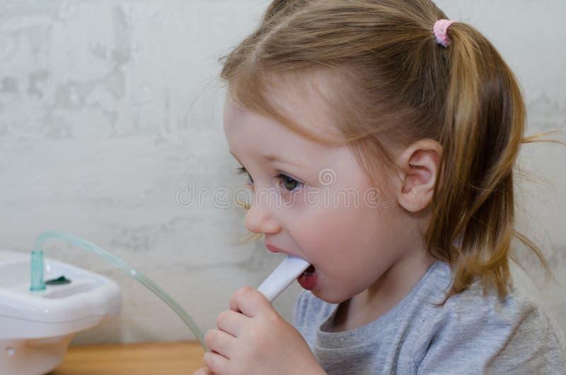 Lilla flickan gör inandning arkivfoto