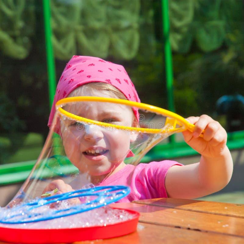 Lilla flickan gör såpbubblor arkivbild