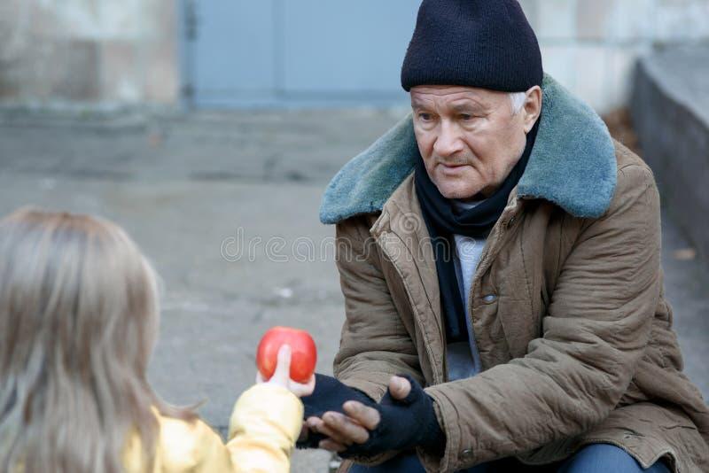 Lilla flickan ger äpplet till tiggaren royaltyfria bilder