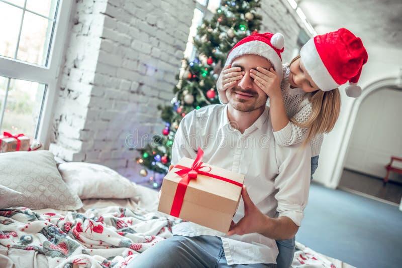 Lilla flickan ger en gåva till pappan hemma med lycklig sinnesrörelse royaltyfri foto