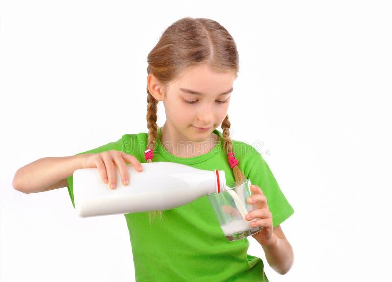 Lilla flickan häller mjölkar från en flaska in i exponeringsglas royaltyfri bild