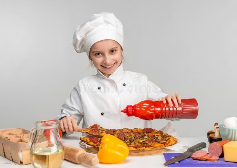 Lilla flickan häller pizza med ketchup royaltyfria foton