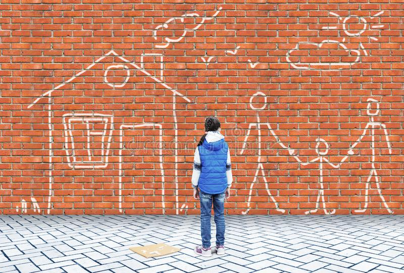 Lilla flickan har dragit intelligenskrita på en väggbild med familjen och huset royaltyfri bild