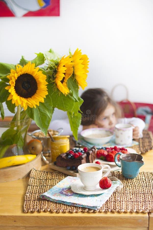 Lilla flickan har frukosten hemma På tabellen är en bukett av blommor av solrosor och en söt paj med frukt, royaltyfria foton