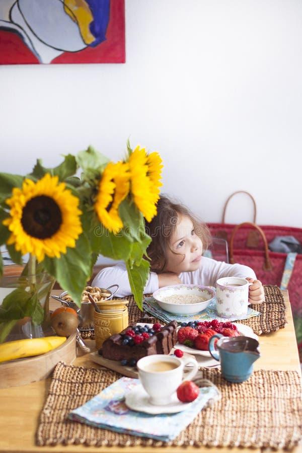 Lilla flickan har frukosten hemma På tabellen är en bukett av blommor av solrosor och en söt paj med frukt, royaltyfri fotografi