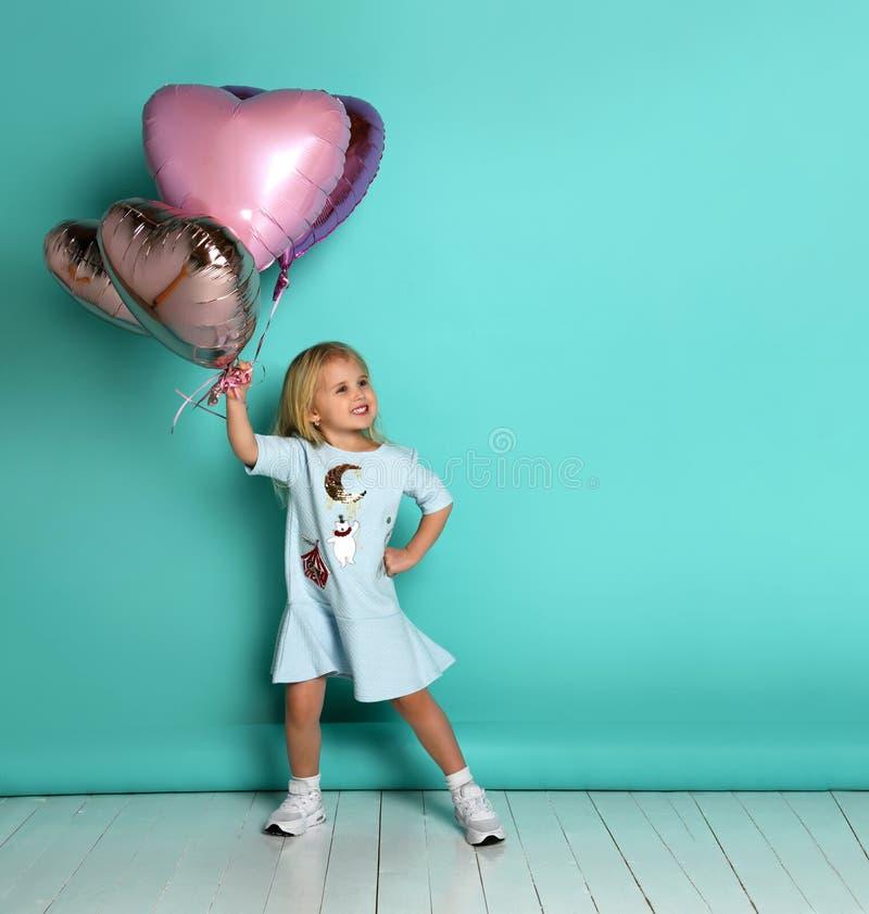 Lilla flickan har gyckel med en grupp av rosa luftballonger i formen av hennes hjärta arkivfoto