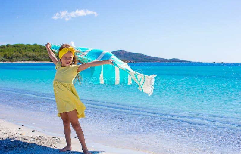 Lilla flickan har gyckel med strandhandduken under royaltyfri fotografi