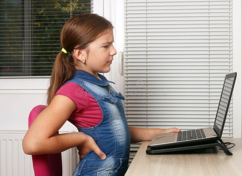 Lilla flickan har tillbaka att smärta, medan genom att använda en bärbar dator arkivfoton