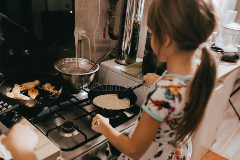 Lilla flickan hjälper hennes moder som lagar mat pannkakor för frukosten i det lilla hemtrevliga köket arkivbilder