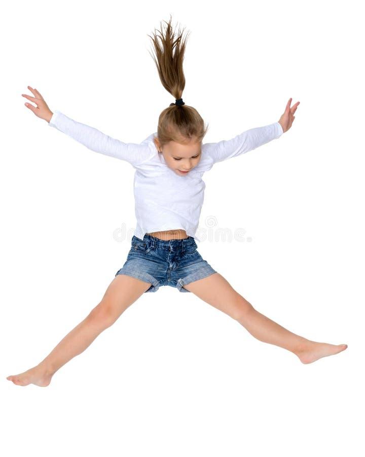 Lilla flickan hoppar arkivfoton