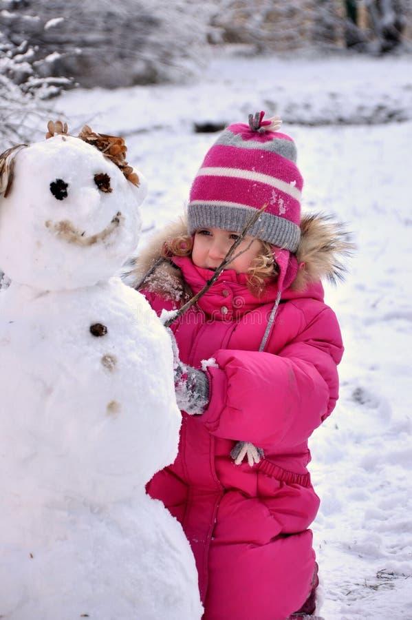 Lilla flickan hugger en snögubbe fotografering för bildbyråer