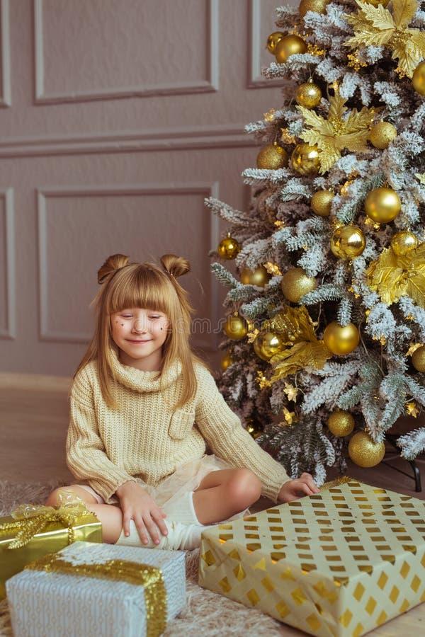 Lilla flickan i beige omslag sitter på ett golv nära askar för en gåva och en julgran royaltyfri foto