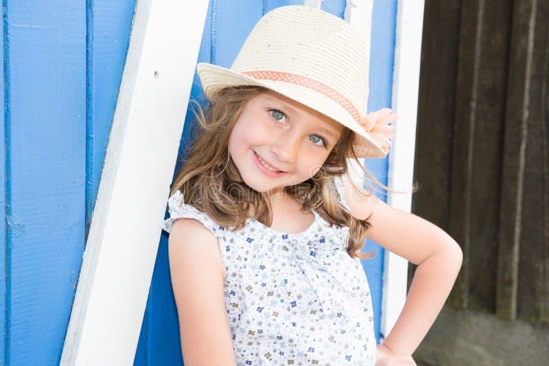lilla flickan i blommor klär, och hatten som kopplar av på stranden nära trä, förlägga i barack sommarsemester och reser begrepp arkivfoto