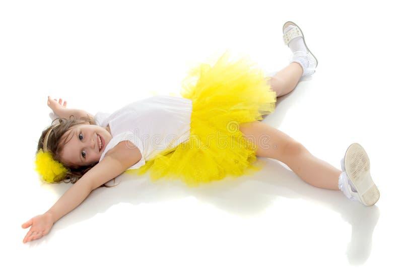 Lilla flickan i den gula kjolen som ligger på golvet royaltyfri bild