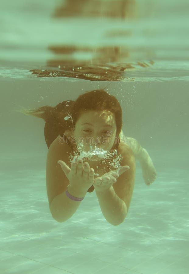 Lilla flickan i den undervattens- hotellpölsimningen och smilin royaltyfria bilder
