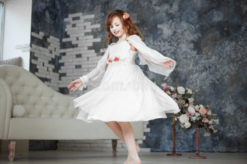 Lilla flickan i den vita klänningen dansing royaltyfria bilder