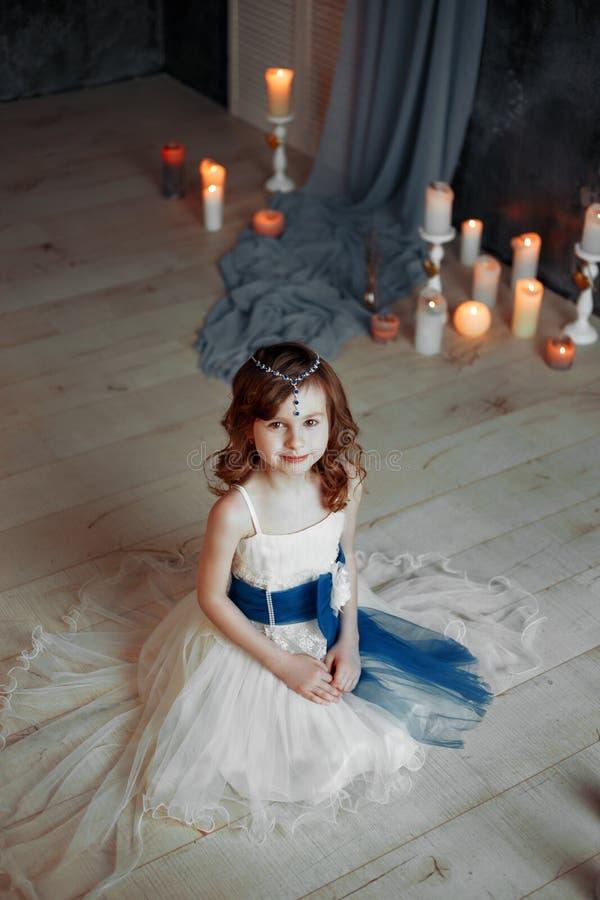 Lilla flickan i den vita klänningen i rum med stearinljusungar ber fotografering för bildbyråer
