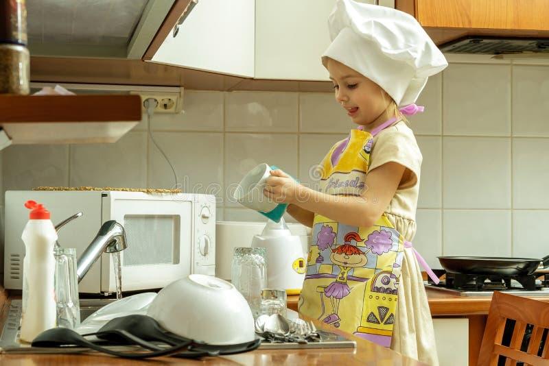 Lilla flickan i den vita kockhatten tvättar disk arkivfoton