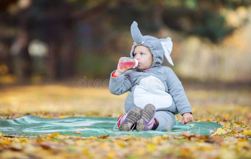 Lilla flickan i elefantdräkt som dricker drycken parkerar in arkivfoton